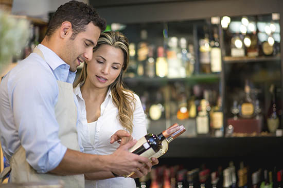 Woman buying a bottle of wine at the supermarket and getting help from the sommelier comparing two kinds